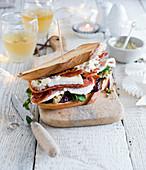 Weihnachts-Sandwich mit Brie, Speck, kaltem Braten und Rucola