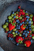 An antique collander filled with strawberries, blueberries, red currants and gooseberries