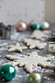 Holiday cookies being made and dusted with flour - with snowflake and star cookie cutters and ornaments sitting beside