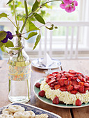 Strawberry cake on a coffee table with floral decorations