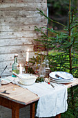 A rustic small table laid outside a wooden hut