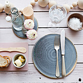A place setting with a blue ceramic plate, butter, salt and bread