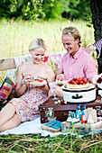 A couple eating strawberry tarts at a picnic