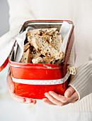 Hände halten alte Brotdose