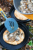 Flatbread with mushrooms cooked in a camping stove