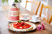 Strawberry tart and coffee on a wooden table