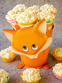 Flower pot with a fox motif filled with cupcakes