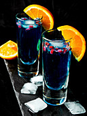 Gin and tonic with Blue Curacao, pomegranate seeds and oranges