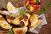 Baked chilean empanadas with beef filling and cherry tomato salad