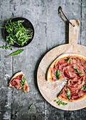 Ham pizza with rocket, sliced