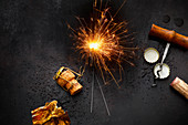 A symbolic image for New Year's Eve: sparklers, champagne, corks and bottle lids