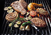 Meat, poultry and vegetables on a grill grate
