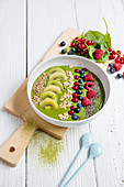 Green smoothie bowl with berries and kiwi