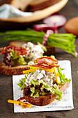 Rustikales Bauernbrot mit Eichblatt-Salat, Katenschinken, Ei, Speck und Käse