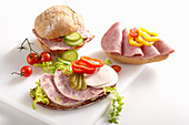 Sliced sausage on bread rolls with vegetables