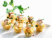 Filo pastry bowls with scrambled eggs, smoked eel, peas and chili