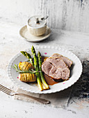 Roast pork with green asparagus on beer gravy