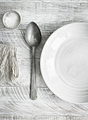 White plate on a table with spoon and salt