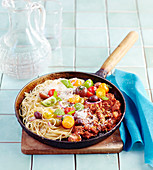 Spaghetti bolognese with cherry tomatoes and basil in a pan