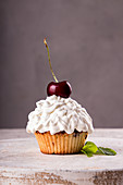 Cupkake with whipped cream decorated with cherry