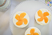 Sponge cakes topped with cream cheese and mandarins
