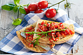 Classic bruschetta from Apulia with tomatoes, basil, olive oil, peperoncini and arugula
