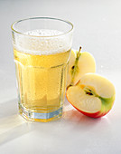 A glass of apple juice spritzer with apple halves