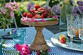 Frisch gepflückte Erdbeeren als essbare Tischdekoration auf Schale mit Fuß