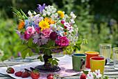 Buntes Blumengesteck auf Tortenplatte als Tischdekoration