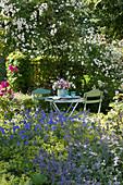 Schattiger Sitzplatz zwischen Rose und Beet mit Storchschnabel, Katzenminze und Frauenmantel