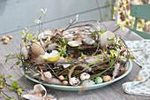 Osterkranz aus Zweigen, dekoriert mit Eierschalen, Federn und Steckzwiebeln