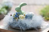 Kleines Osternest aus Federn mit Sträußchen aus Narzisse, Vergißmeinnicht und Gänseblümchen