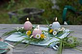 Kleine Tischdeko mit Osterkerzen in Blütenkränzchen