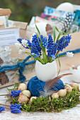 Kleiner Strauß aus Traubenhyazinthen in Gänseei als Vase, Garnrolle im Mooskranz mit Steckzwiebeln und Feder