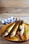 Smoked mackerel on a wooden board with a knife and napkin