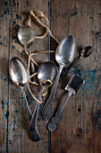 Various silver spoons on a wooden surface