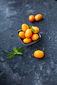 Kumquats in a small bowl with mint