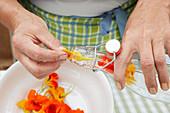 Blüten von der Kapuzinerkresse in eine Bügelflasche geben