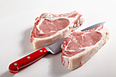 Two raw veal cutlets with a knife