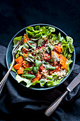 A salad bowl with lettuce, pumpkin and quinoa
