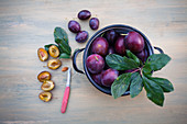 Fresh plums in a pot and stones on a wooden background