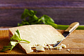 Pecorino sardo, hard cheese made from sheep's milk (Sardinia) on a wooden board with a knife