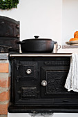 Antique, cast iron, wood-burning stove in country-house kitchen