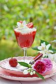 Erdbeermus im Stielglas und Blüten