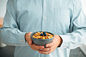 Mann hält Joghurtmüsli mit Trockenfrüchten und Heidelbeeren
