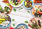 Greek food: Meze, gyros, souvlaki, fried fish, pita, greek salad, tzatziki, assortment of feta, olives and vegetables