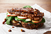 Marinated Lupini Bean Tempeh open-faced sandwich with sliced apple, spinach and grilled onions