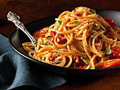 Spaghetti pasta with tomatoes and herbs in black bowl with fork