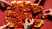 Roman style pizza topped with tomatoes and crushed red pepper flakes with hands (one tattooed)