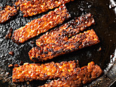 Tempeh bacon strips in cast-iron skillet